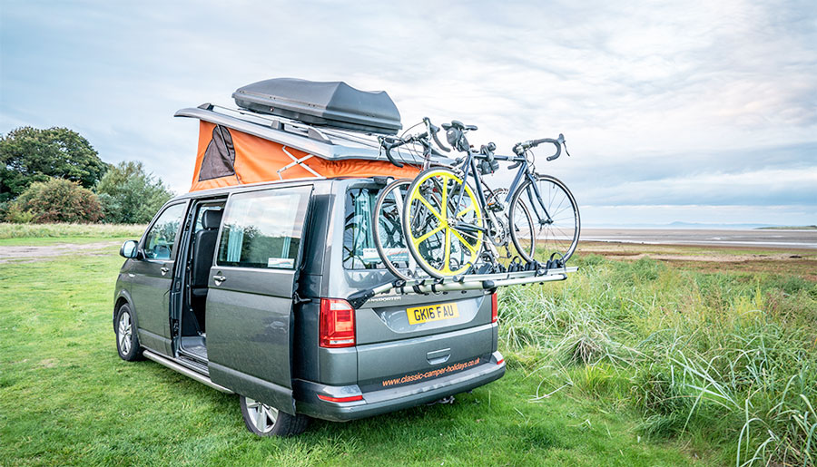Campervan by the beach with bikes on the back